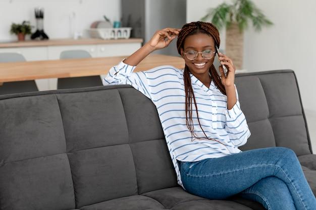Donna sorridente che parla al telefono inquadratura media