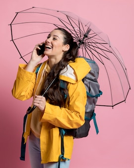 Smiley woman talking on the phone while holding an umbrella