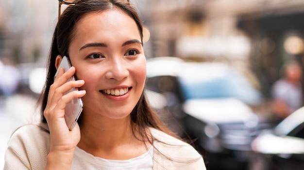 Donna di smiley che parla sullo smartphone all'aperto