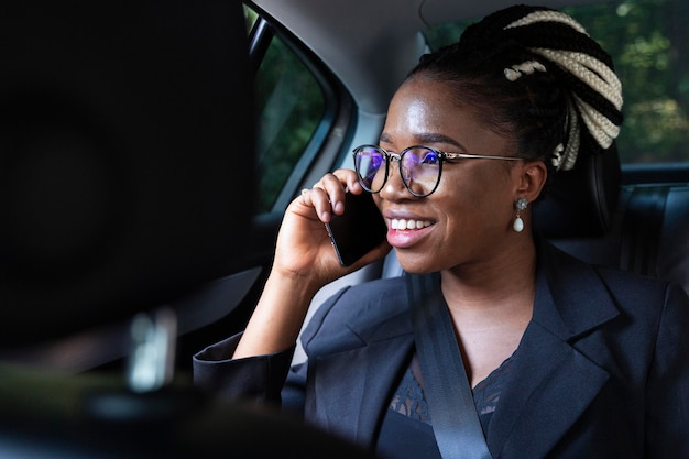 Smiley woman talking on smartphone while in her car