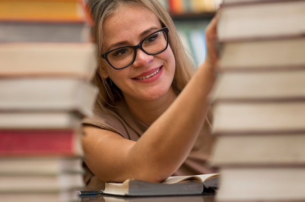 Smiley woman touching books