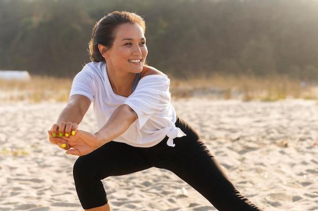 ビーチでスマイリー女性のトレーニング