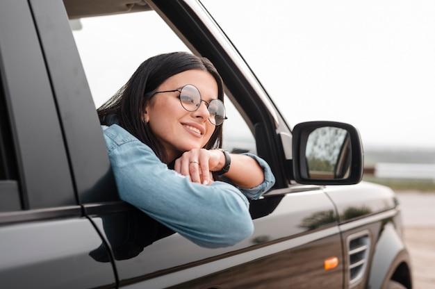 Donna sorridente che viaggia da sola in auto