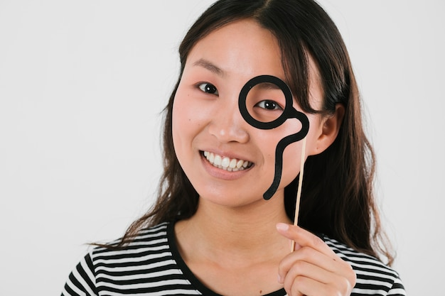 Smiley woman trying out fake monocle
