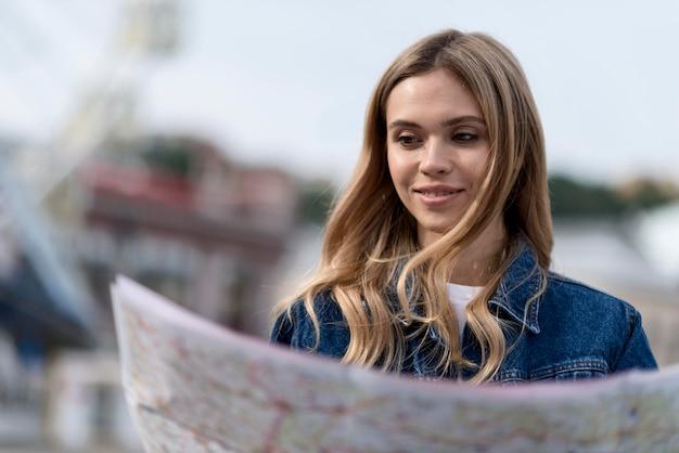 Donna sorridente utilizzando una mappa sfocata
