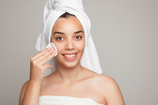Smiley woman using a cotton pad on her face