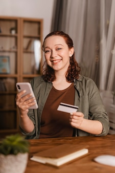 Смайлик женщина с помощью кредитной карты и смартфона дома