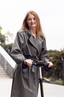 Смайлик женщина с помощью электрического скутера на открытом воздухе