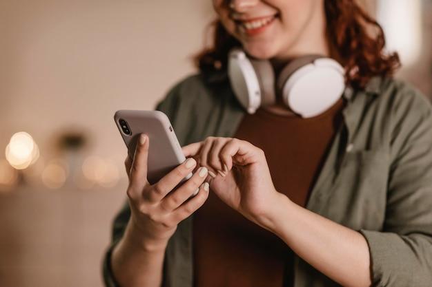 Улыбающаяся женщина с помощью своего смартфона и наушников дома