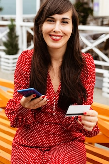 스마트 폰 및 신용 카드를 사용하여 온라인 쇼핑 판매에 웃는 여자