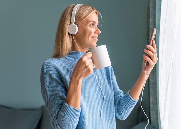 パンデミック時にコーヒーを飲みながら自宅でスマートフォンとヘッドフォンを使用してスマイリー女性
