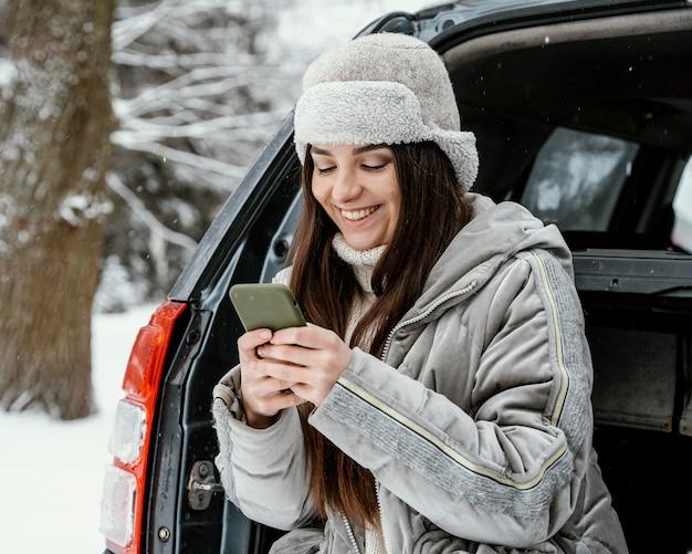 Donna sorridente che utilizza smartphone durante un viaggio su strada