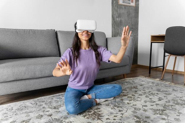 Donna sorridente utilizzando le cuffie da realtà virtuale a casa