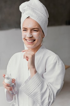 Smiley woman using a white face cream