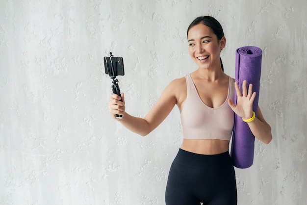 Смайлик женщина ведет видеоблог со своим телефоном, держа в руках фитнес-коврик