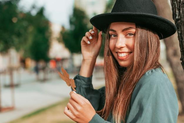 Donna sorridente che indossa un cappello nero con copia spazio