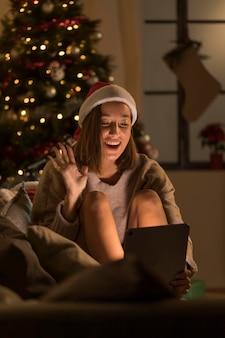 Smiley woman wearing santa hat waving at tablet