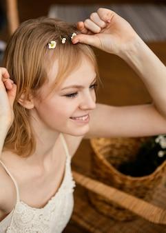 Donna sorridente che indossa una corona di fiori di primavera