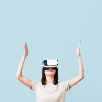 Smiley woman wearing virtual reality headset with copy space
