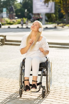 Smiley woman in wheelchair listening to music on headphones outdoors