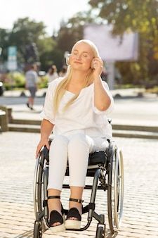 Smiley woman in wheelchair listening to music on headphones outside