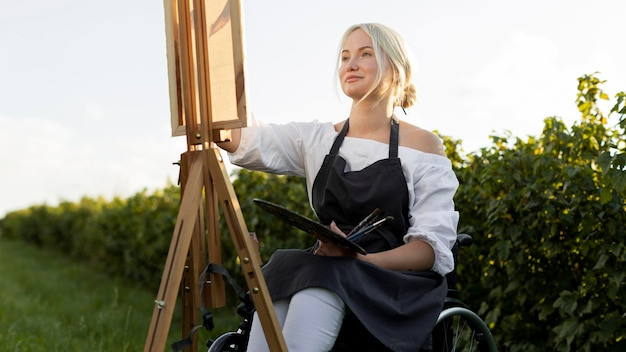 Smiley woman in wheelchair outdoors in nature with canvas and palette