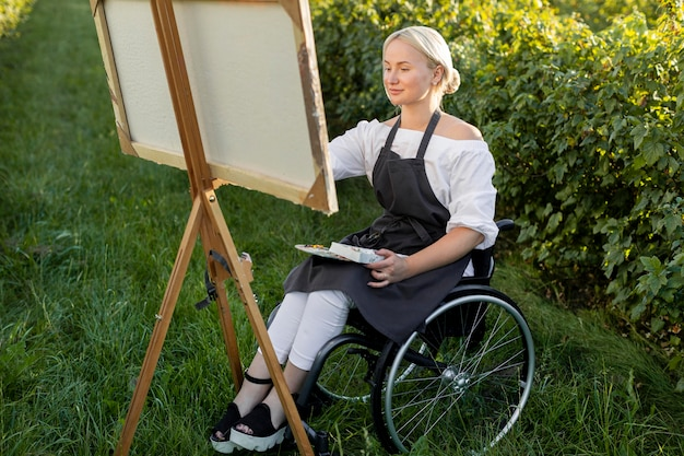 Smiley woman in wheelchair painting in nature