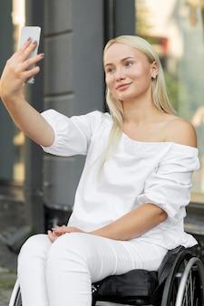 Donna di smiley in sedia a rotelle prendendo selfie con lo smartphone