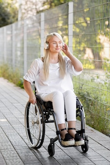 Smiley woman in wheelchair with headphones outdoors