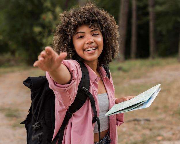 地図を保持しながらポーズをとってバックパックを持つスマイリー女性