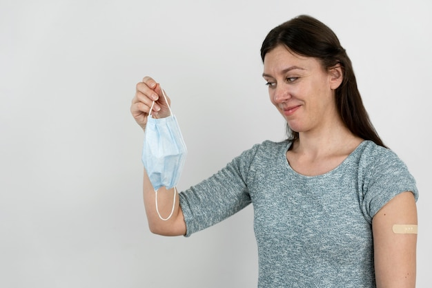 Smiley woman with bandage on arm after vaccine shot holding medical mask