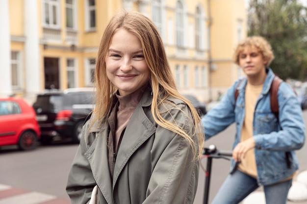 Donna sorridente con il ragazzo su scooter elettrico all'aperto
