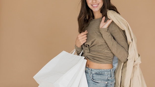 Smiley woman with coat on shoulder and shopping bags