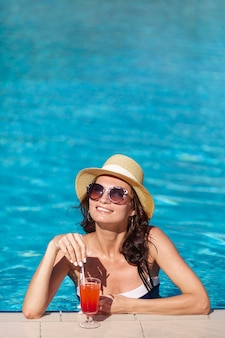 Smiley woman with a cocktail sitting in a pool