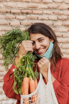 Smiley woman with face mask outdoors holding carrots