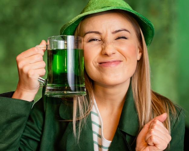 Smiley woman with hat celebrating st. patrick's day with drink at the bar