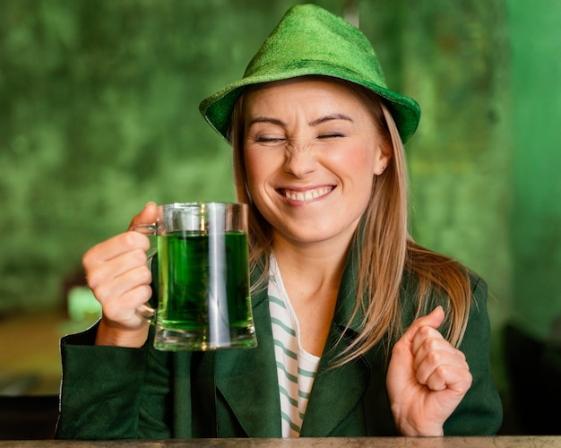 Smiley woman with hat celebrating st. patrick's day with drink