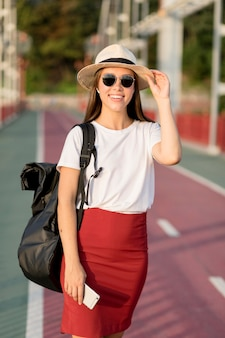 Smiley woman with hat and sunglasses holding smartphone while traveling
