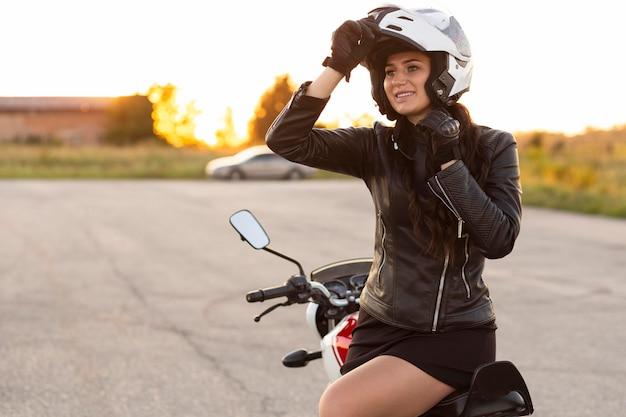 彼女のバイクに座っているヘルメットを持つスマイリー女性