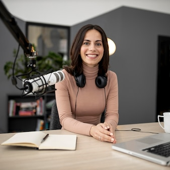 Smiley woman with microphone and notebook in a radio studio