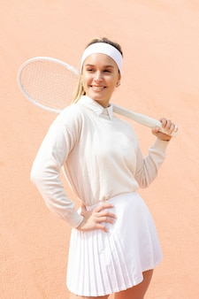 Smiley woman with racket for tennis