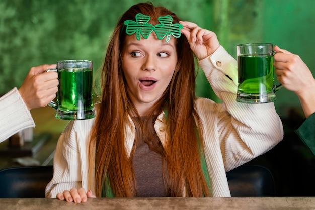 Donna sorridente con occhiali trifoglio che celebra st. patrick's day al bar con bevande