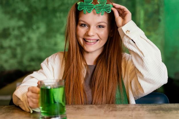 Donna sorridente con occhiali trifoglio che celebra st. la giornata di patrick al bar