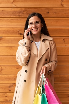 Smiley woman with shopping bags talking on the phone