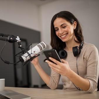 라디오 스튜디오에서 스마트 폰 및 마이크와 웃는 여자
