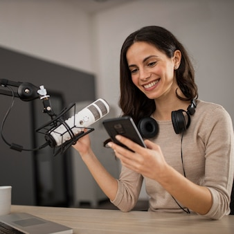 Smiley woman with smartphone and microphone in a radio studio