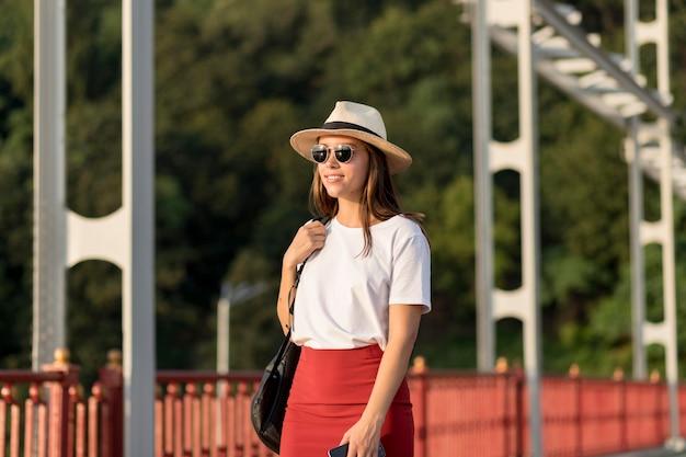 Смайлик женщина в солнцезащитных очках и шляпе путешествует в одиночку