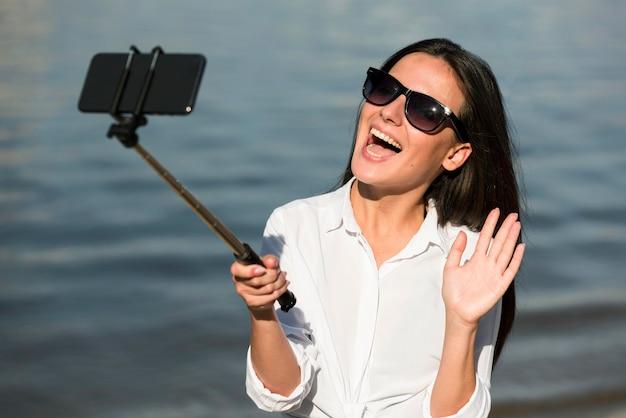Donna di smiley con gli occhiali da sole che prendono selfie in spiaggia