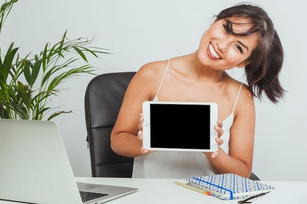 Donna di smiley con una tavoletta in ufficio