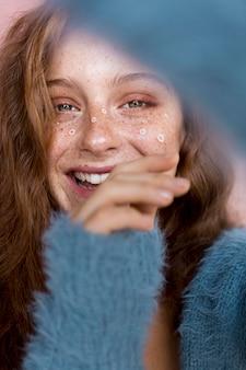 彼女の顔に白い花を持つスマイリー女性